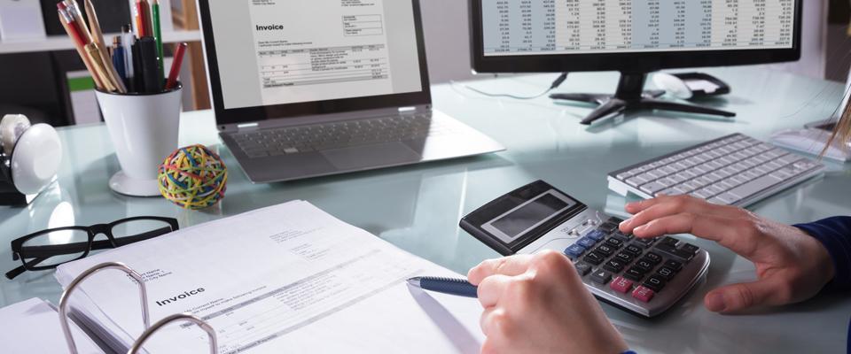 Praca przy kalkulatorze, dokumentach ilaptopie
