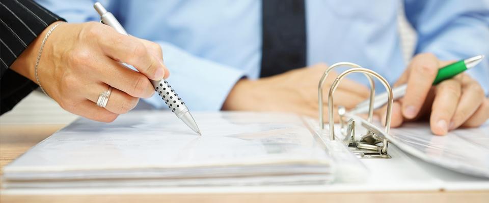 Kobieca ręka podpisująca dokumenty